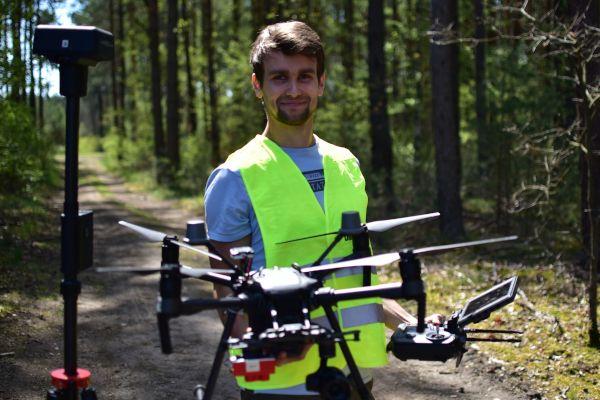 Zastosowanie dronów w leśnictwie. Grzegorz Czerwczak z firmy Era Dronów prowadzi szkolenie z obsługi dronów na tle lasu.