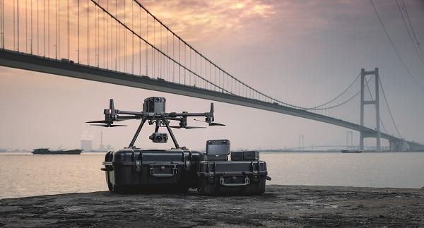 Dron DJI Matrice 300 RTK, walizki, kamery, akumulatory, akcesoria nad wodą na tle mostu