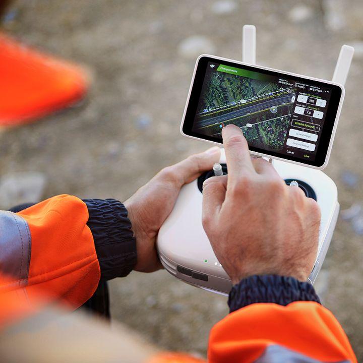 Dron dla geodety. Geodeta obsługuje loty dronem przy pomocy kontrolera DJI Phantom 4 RTK