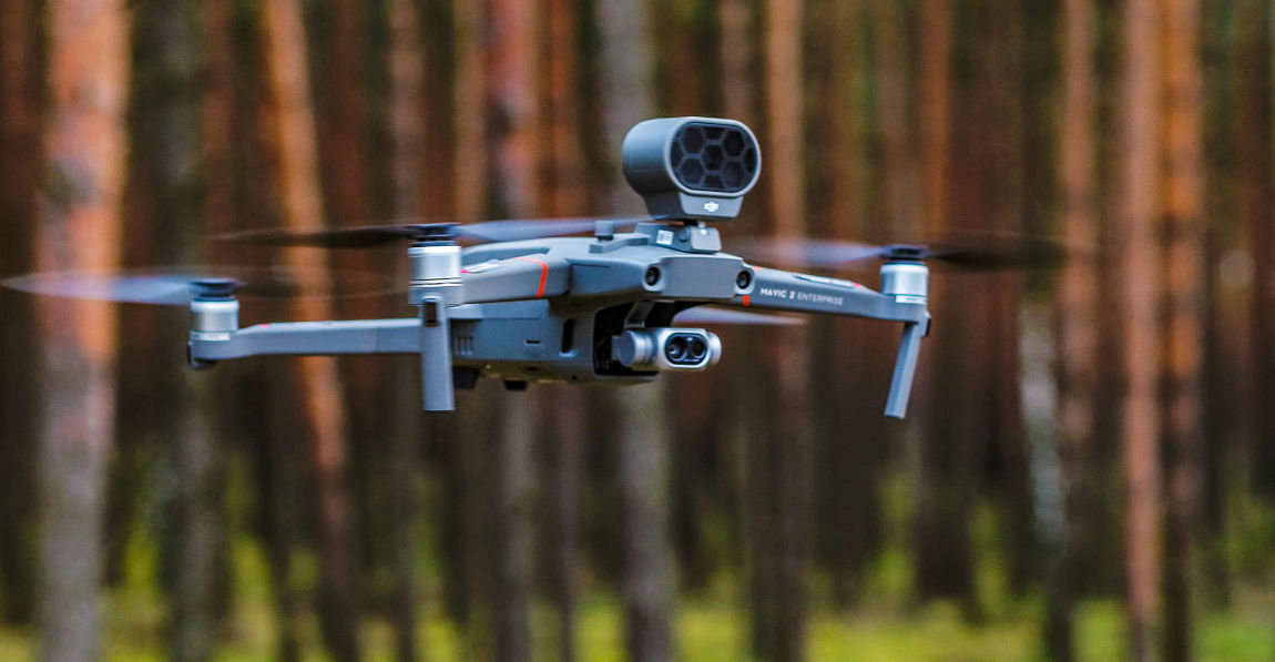 Dron z kamerą termowizyjną leci na tle lasu
