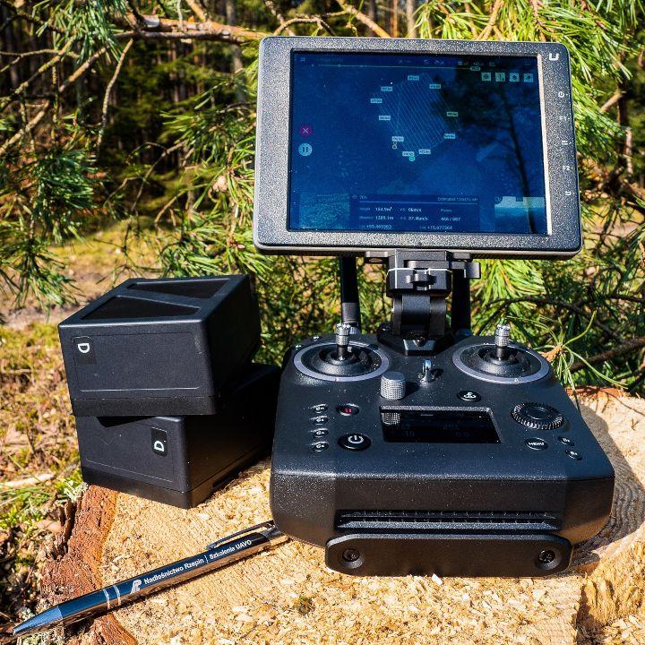 Wykorzystanie dronów w leśnictwie. Na pniu drzewa leżą kontroler DJI Cendence S, monitor DJI Crystalsky, akumulatory TB55.